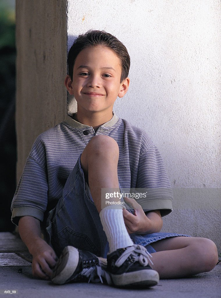 a boy wearing denim shorts and a gray striped shirt leans against a wall as he sits and smiles : Stockfoto