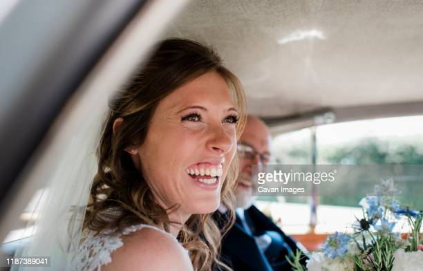 a bride laughing in her car on her wedding day - anniversary stock pictures, royalty-free photos & images