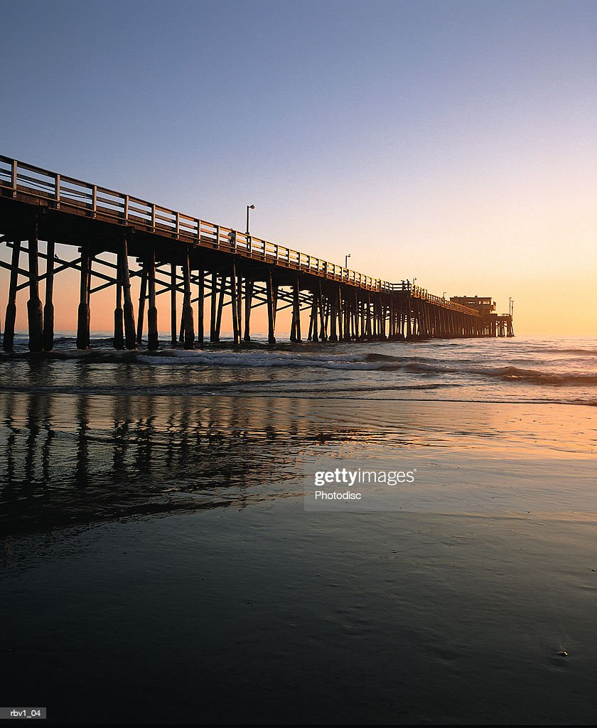 a bridge rises above the ocean waves as the sun sets over the horizon under a blue sky : Stockfoto