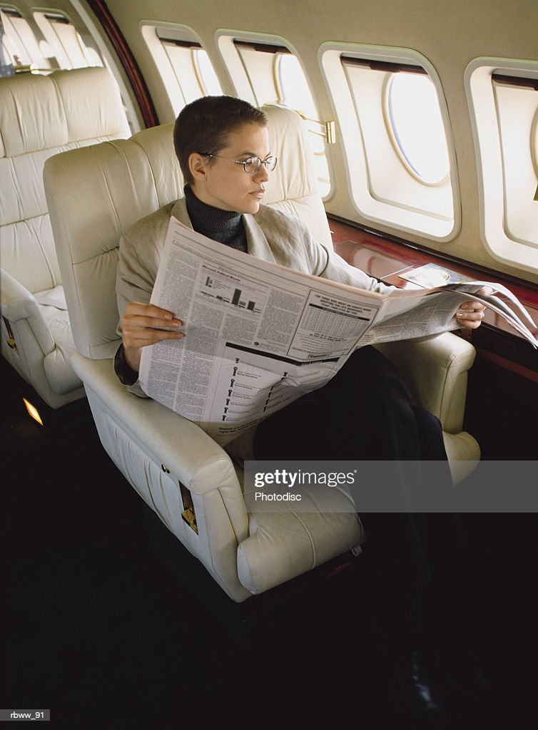a brunette caucasian woman reads a newspaper while sitting on an airplane : Foto de stock