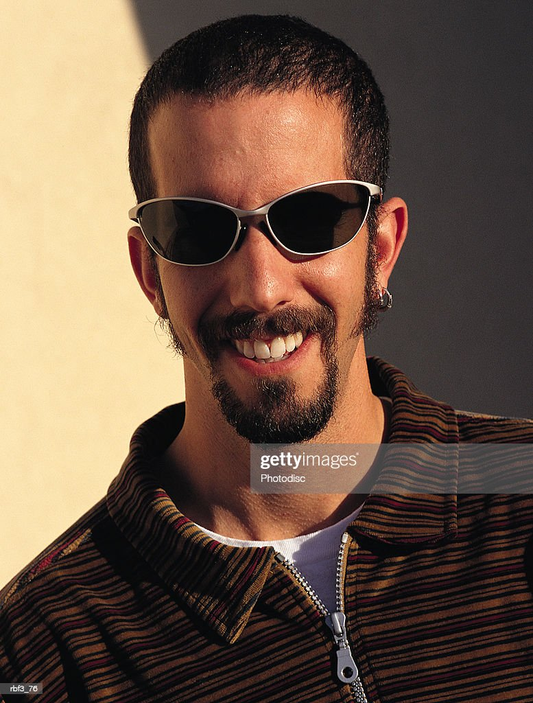 a brunette college-aged man wearing a striped shirt and sunglasses smiles : Stockfoto
