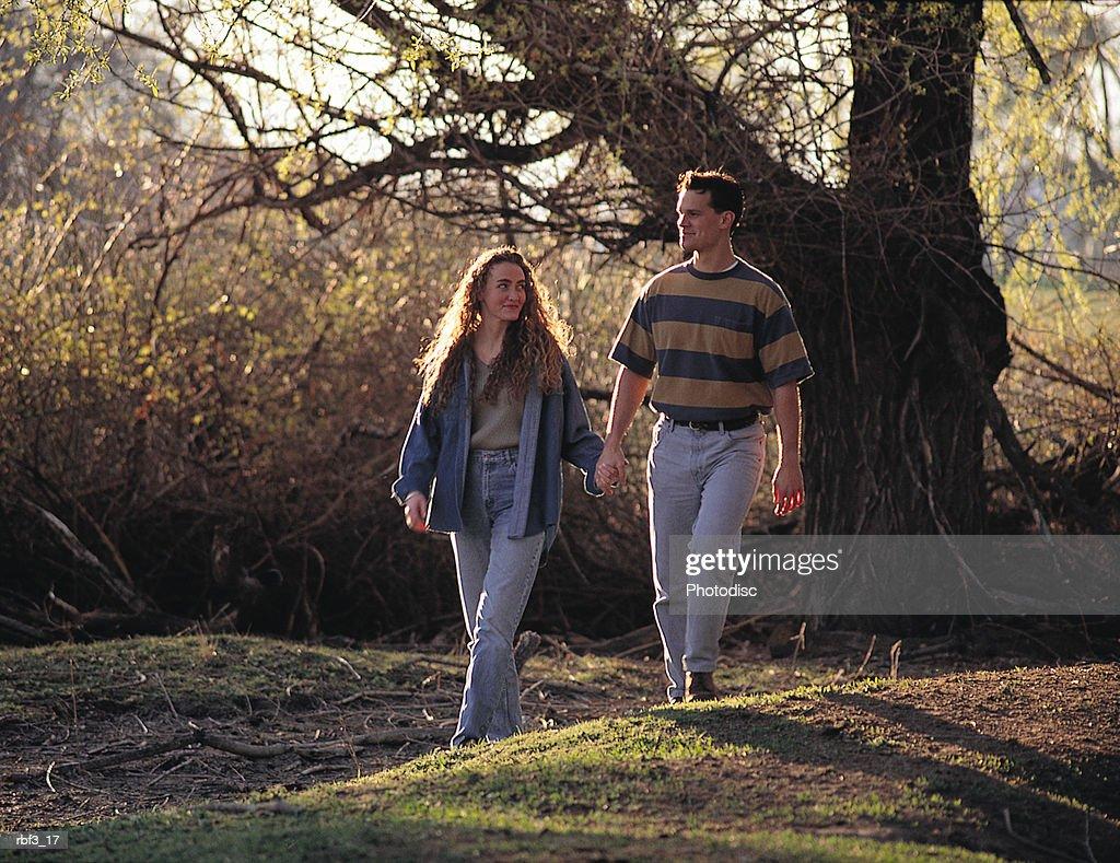a brunette woman wearing jeans walks hand in hand with a man wearing jeans and a striped shirt on a green path : Stockfoto