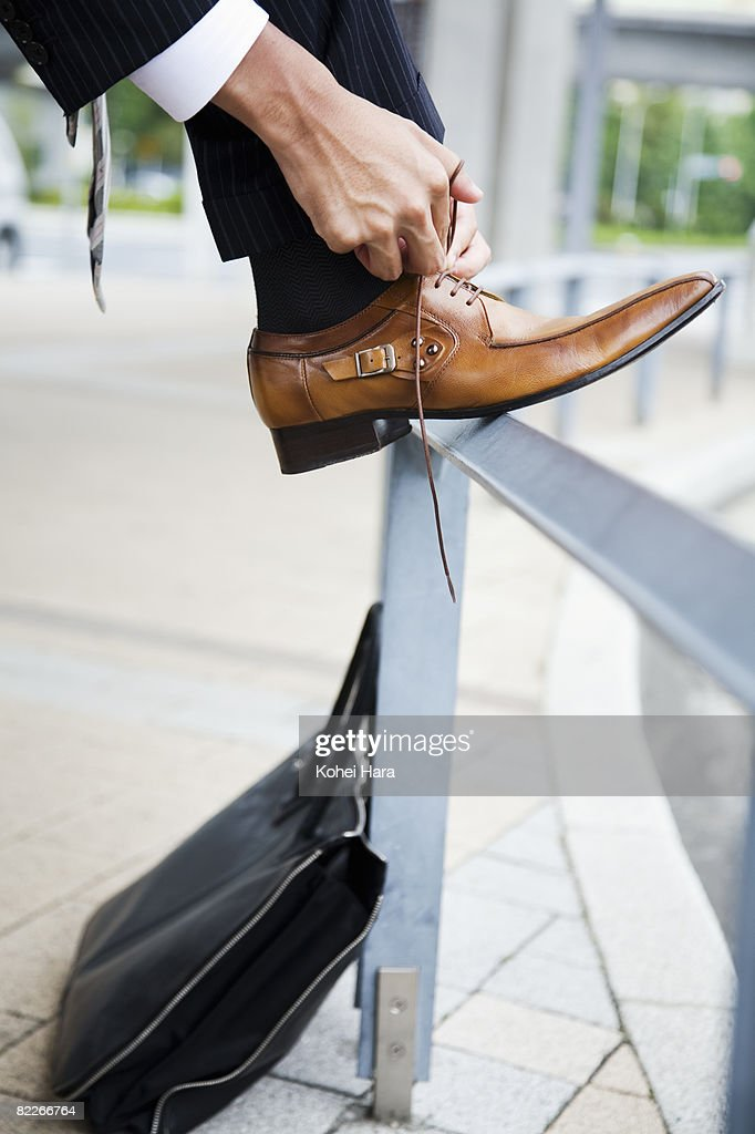 a business man tying a shoelace : Stock Photo