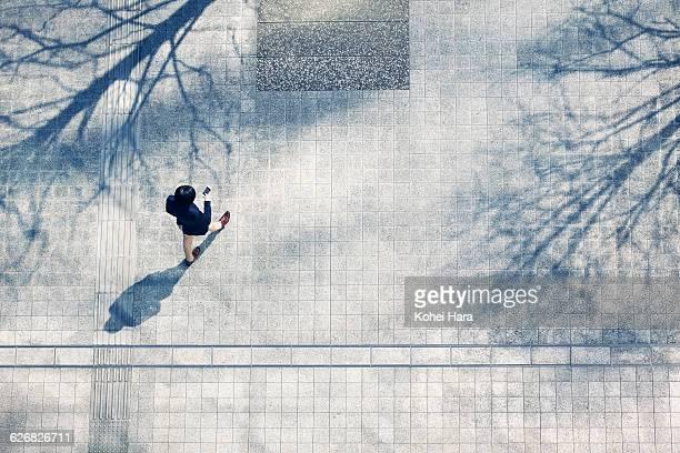 a business man walking in the business district - städtischer platz stock-fotos und bilder