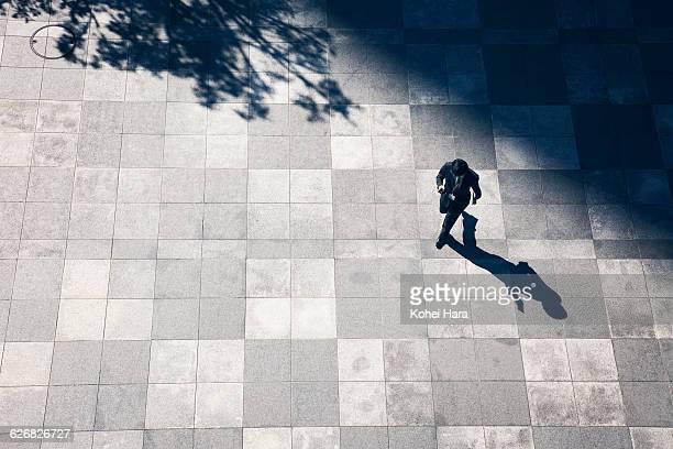 a business man walking in the business district - pedone ruolo dell'uomo foto e immagini stock