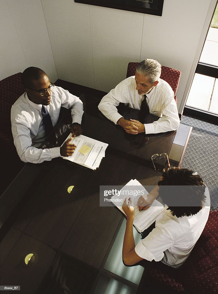 a businesswoman and two businessmen meet in an office to discuss their work : Foto de stock