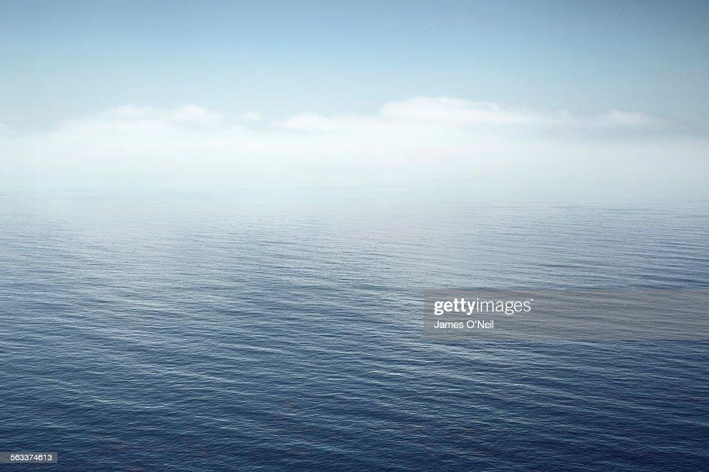 a calm sea fading into the sky : Foto de stock