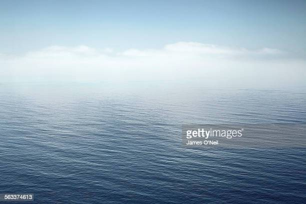 a calm sea fading into the sky - meer stock-fotos und bilder