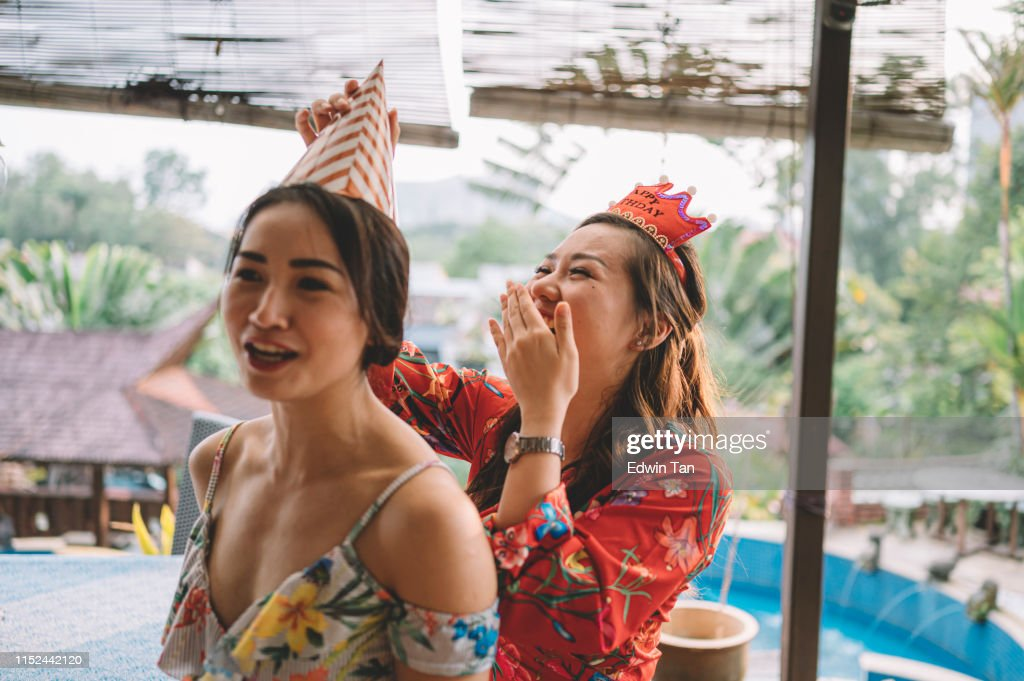 a candid moment where an asian chinese female helping her sister to tie up the party hat getting ready for the birthday celebration event : Stock Photo