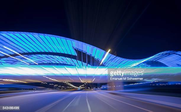 POV of a car approaching a blue illuminated bridge