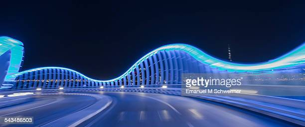 POV of a car driving on a illuminated blue bridge