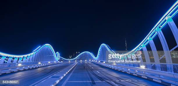 POV of a car resting on a illuminated blue bridge
