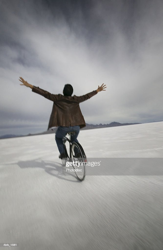 a carefree man in a business suit rides a bike through the open nothingness of a desert : Stockfoto