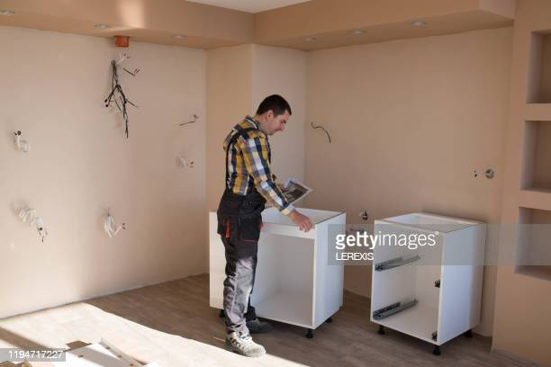 a carpenter is preparing to install a kitchen - lerexis stock pictures, royalty-free photos & images