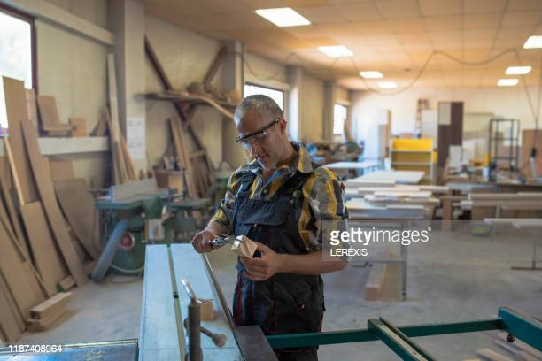 a carpenter measures a piece of wood that he just cut - crash site stock pictures, royalty-free photos & images