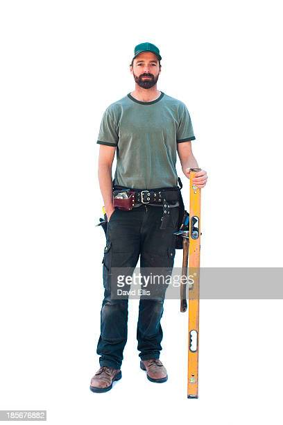 a carpenter stands with his tool belt and holds a level