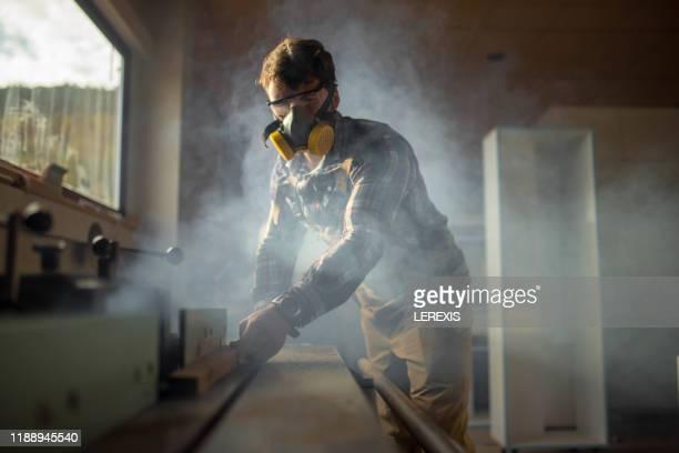 a carpenter works on a woodworking machine - kunsthandwerker stock-fotos und bilder