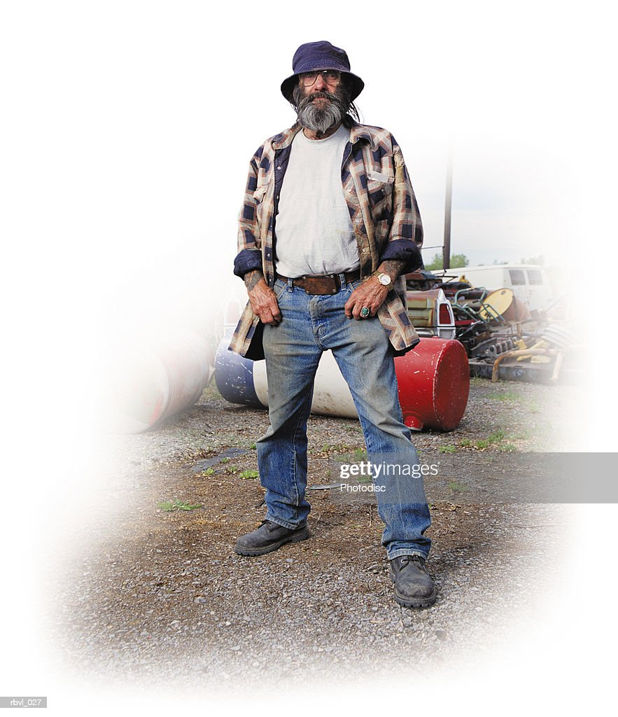 a casually dressed older caucasian man with long facial hair wearing dirty jeans and a floppy hat is standing in a yard full of junk : Foto de stock