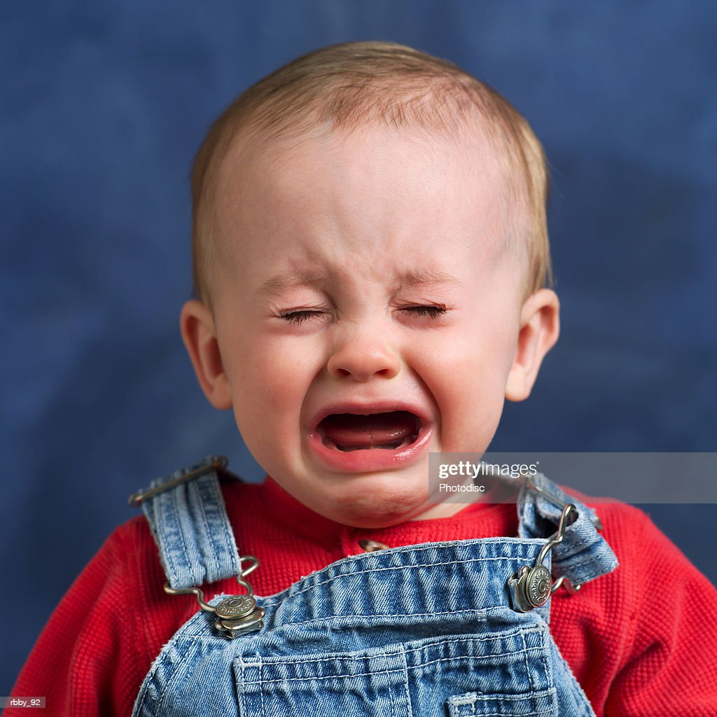 a caucasian baby begins to cry loudly : Stock Photo
