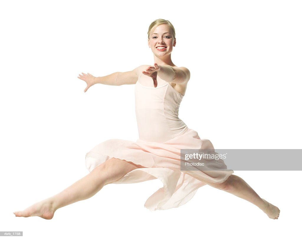 a caucasian blonde female teen in a pink ballet outfit jumps out in a dance routine : Stockfoto