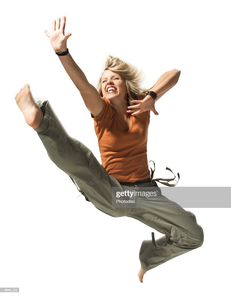 a caucasian blonde female teen in green pants and an orange shirt jumps up in the air : Foto de stock