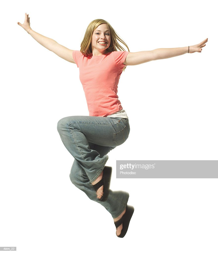 a caucasian blonde female teen in jeans and a pink shirt jumps up and throws her arms out : Foto de stock