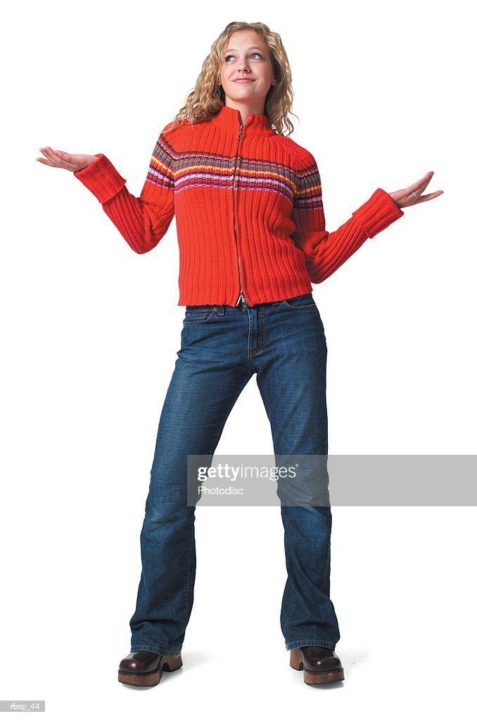 a caucasian blonde female teen in jeans and a red sweater tosses her arms out to the side : Foto de stock