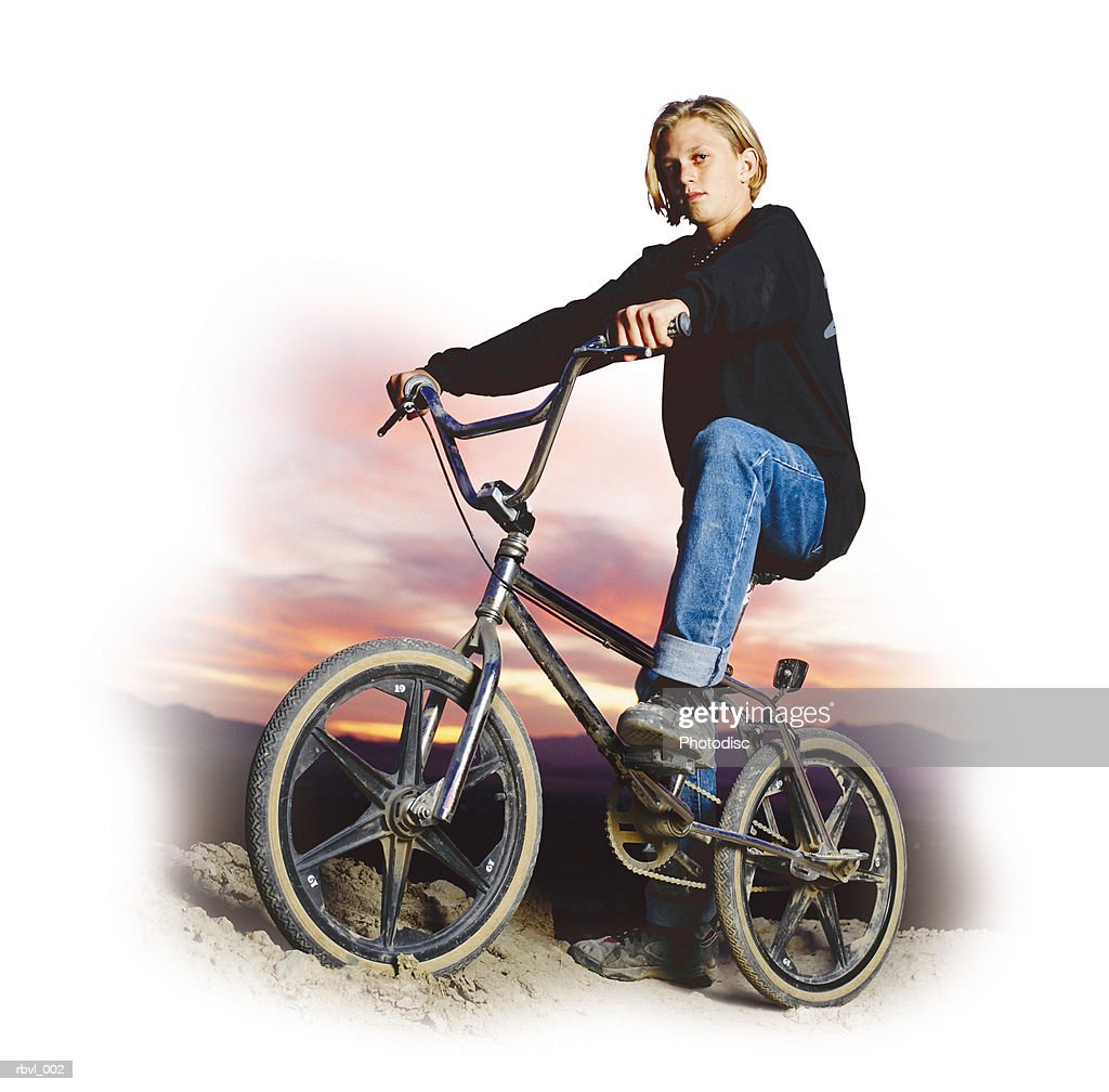 a caucasian boy in a black shirt and blue jeans is sitting on a freestyle bicycle with the sun setting behind him : Foto de stock