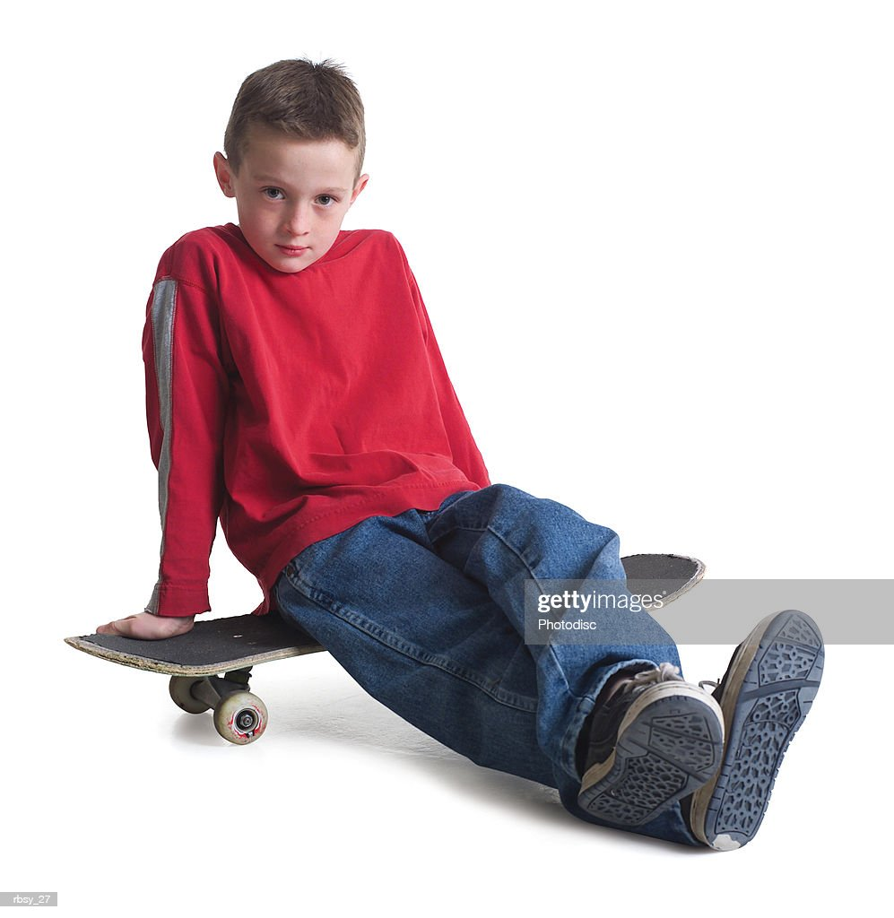 a caucasian boy in jeans and a red sweater sits on his skateboard and smiles slightly : Stock Photo