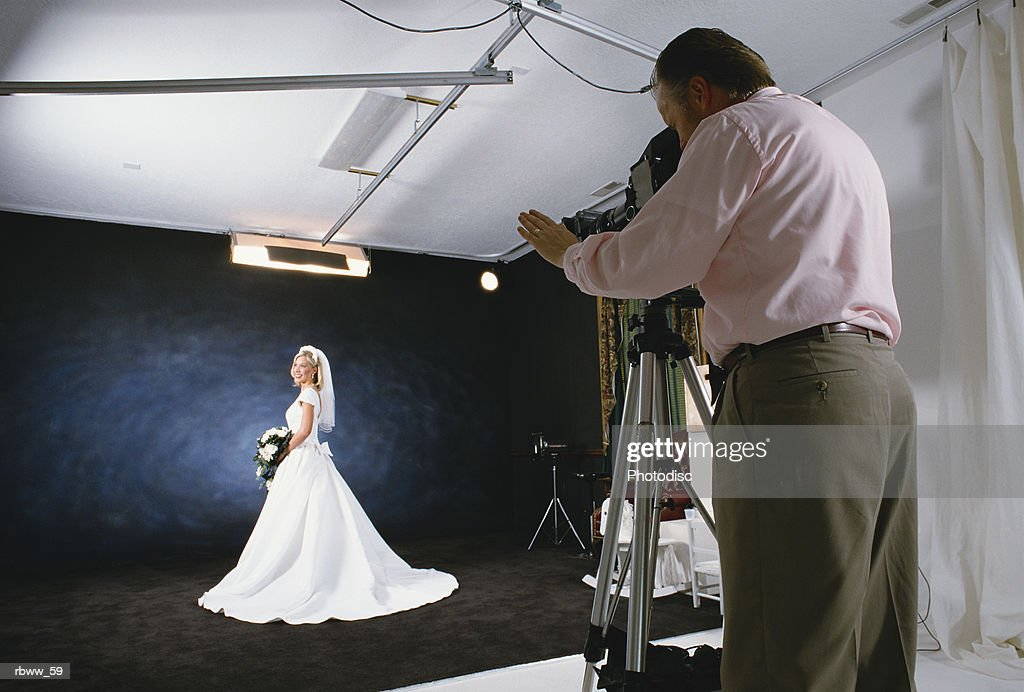 a caucasian bride poses in her bridal gown for a photographer in his studio : Foto de stock