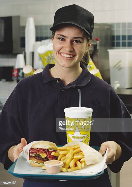 a caucasian brunette fast food employee smiles while holding a tray of food - serving tray stock pictures, royalty-free photos & images