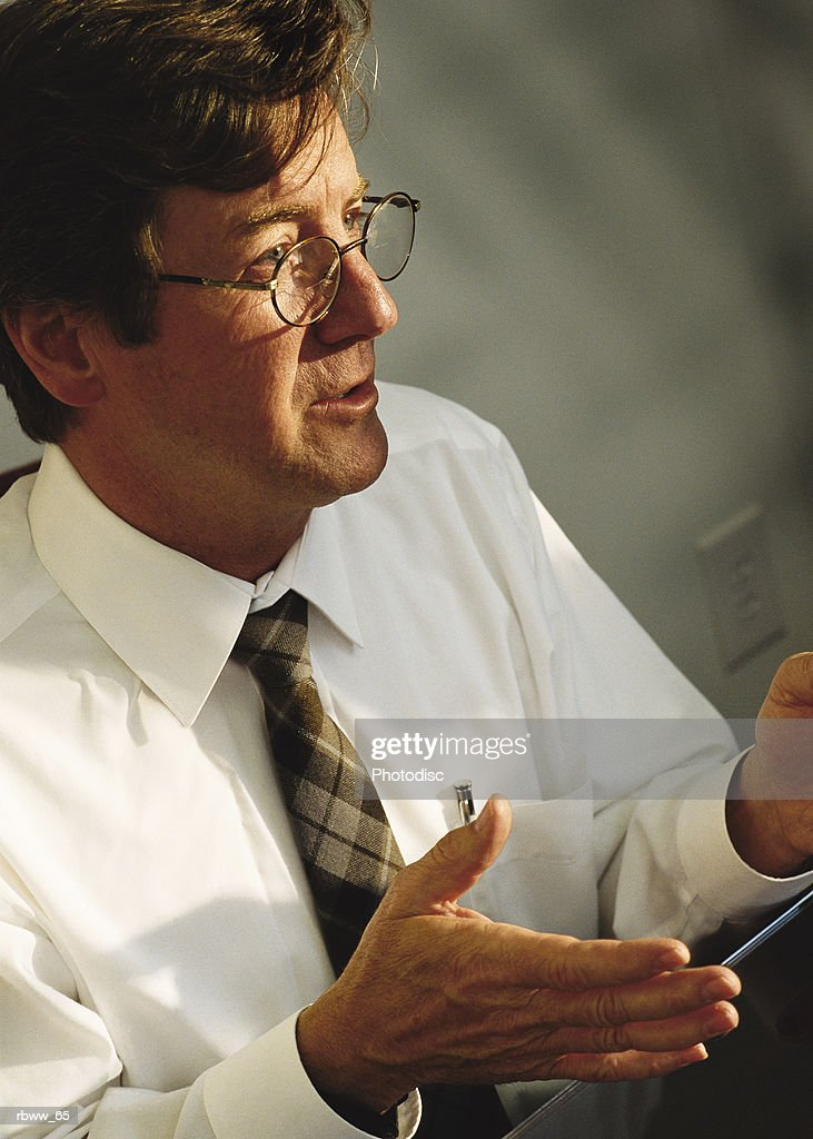 a caucasian buisnessman speaks while motioning with his hands : Foto de stock