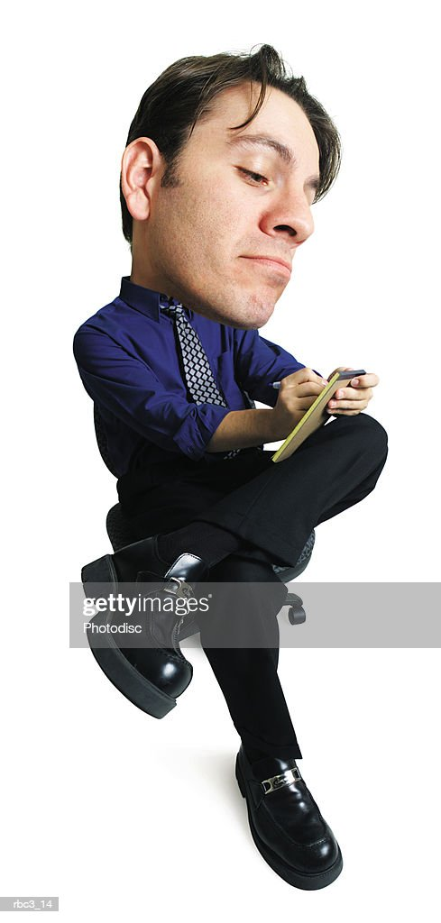 a caucasian business man in a blue shirt and black slacks sits with  his legs crossed and writes on a notepad : Stockfoto