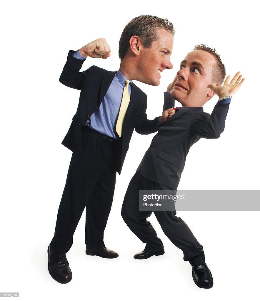 a caucasian business man in a blue shirt and dark suit grabs a co-worker by his collar and reaches back to punch him while the co-worker leans back and surrenders : Stock Photo