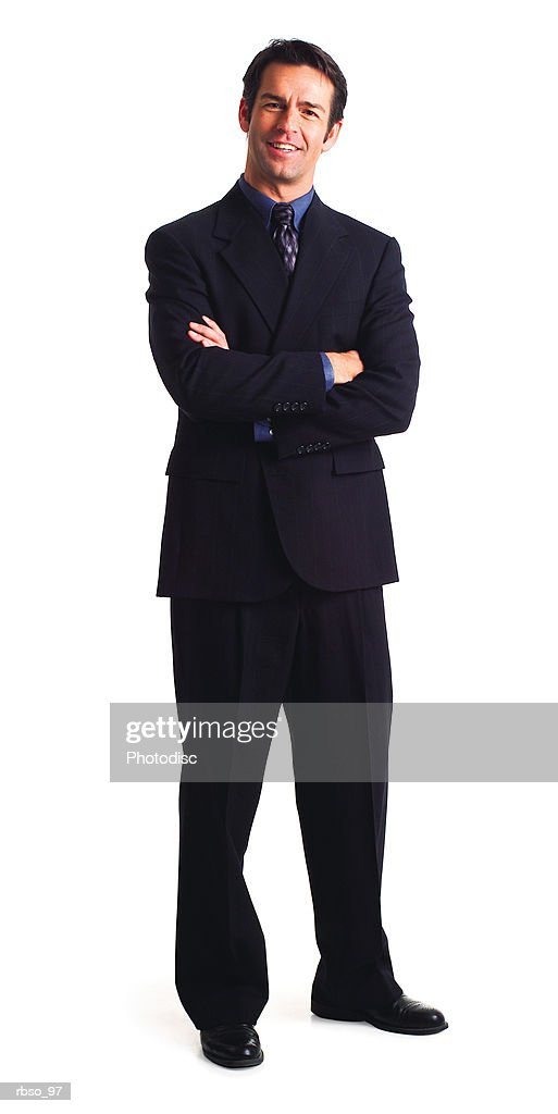a caucasian business man in a dark suit folds his arms and smiles : Stockfoto