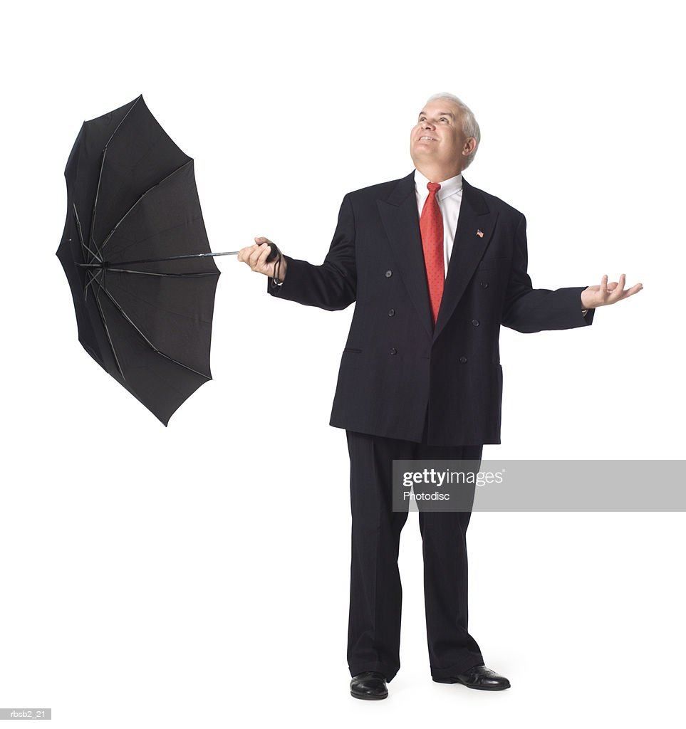 a caucasian business man in a dark suit holds an umbrella and looks upward : Foto de stock