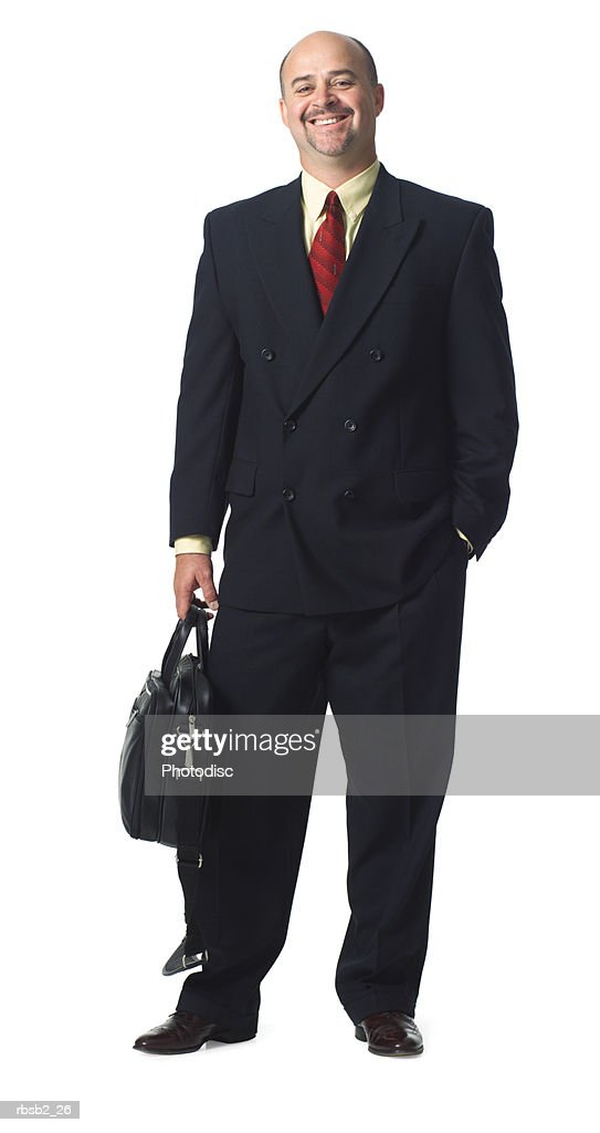 a caucasian business man in a dark suit holds his computer bag and smiles : Foto de stock