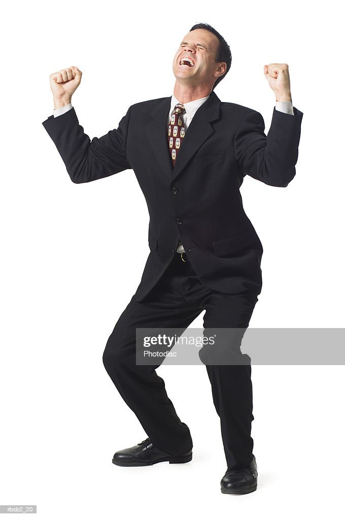 a caucasian business man in a dark suit holds up his arms in celebration : Foto de stock