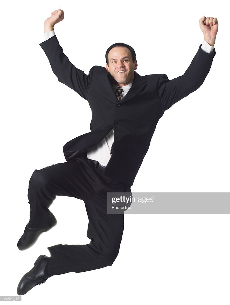 a caucasian business man in a dark suit jumps playfully up into the air : Stockfoto