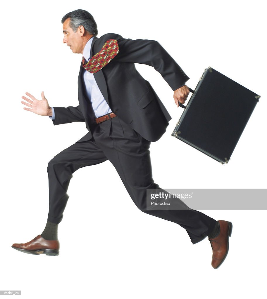 a caucasian business man in a dark suit runs briskly holding his briefcase : Foto de stock