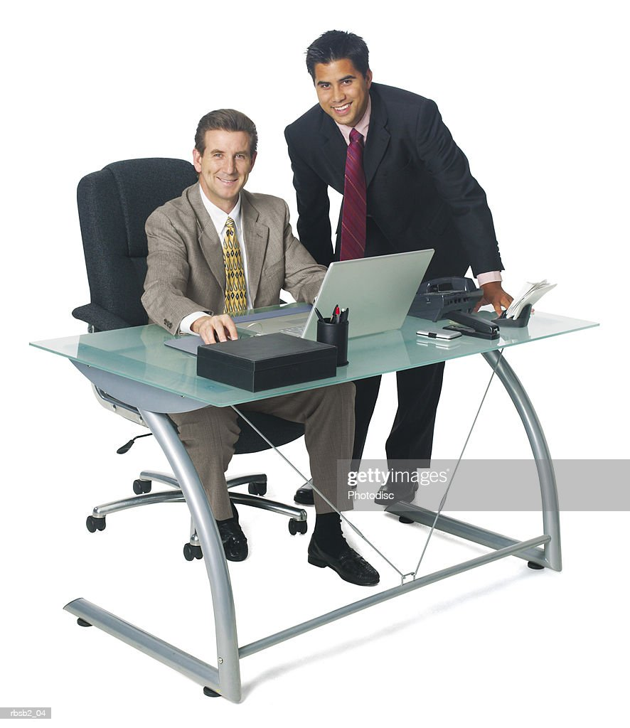 a caucasian business man sits at his desk and converses with a coworker as they both smile : Foto de stock