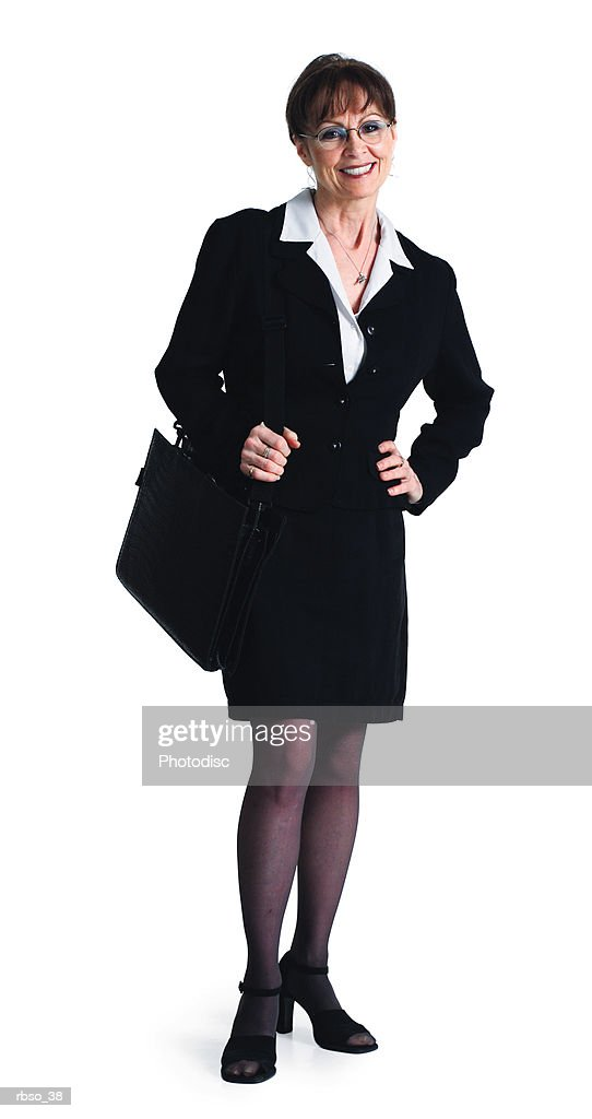 a caucasian business woman dressed in black holds her bag and smiles : Foto de stock