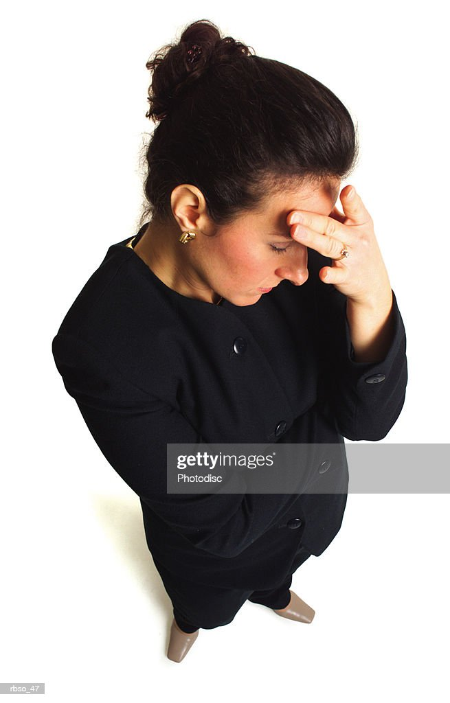 a caucasian business woman holds her head as if stressed as the camera looks down on her : Foto de stock