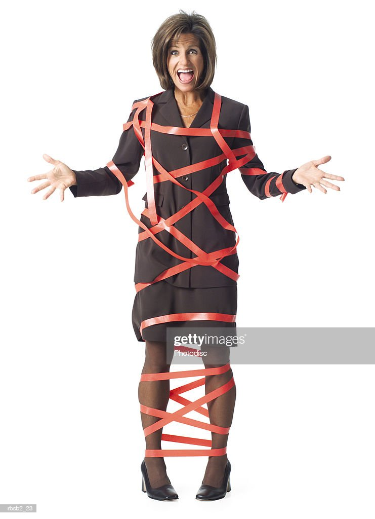 a caucasian business woman in a brown dress reacts to being caught up in red tape : Foto de stock