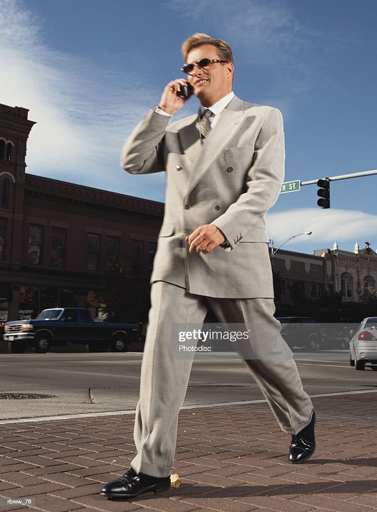 a caucasian businessman crosses a downtown street while talking on a cell phone : Foto de stock