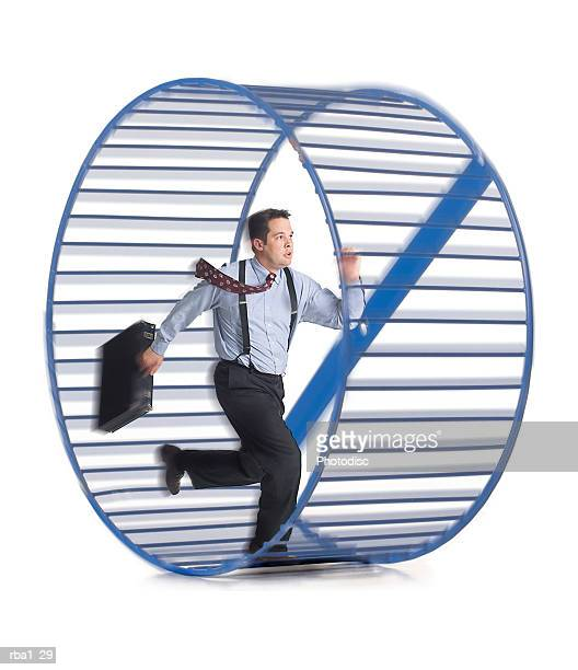 a caucasian businessman in a shirt and tie as he runs around in circles in a hamster wheel