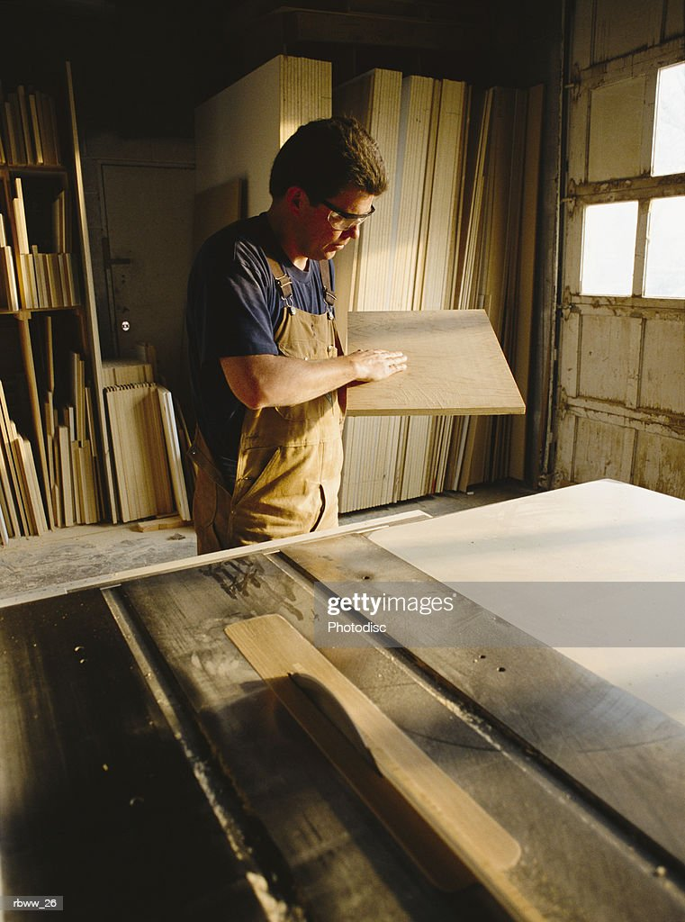 a caucasian  carpender inspects a rectangular board : Stockfoto