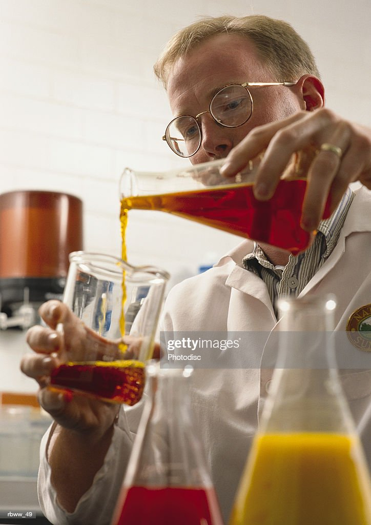 a caucasian chemist in a laboratory pours colorful liquids from one beaker to another : Foto de stock