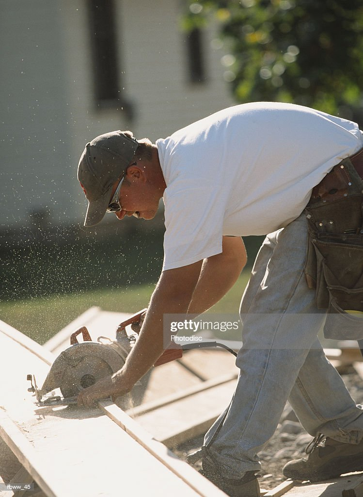 a caucasian construction worker uses a skillsaw to cut a  board : Foto de stock