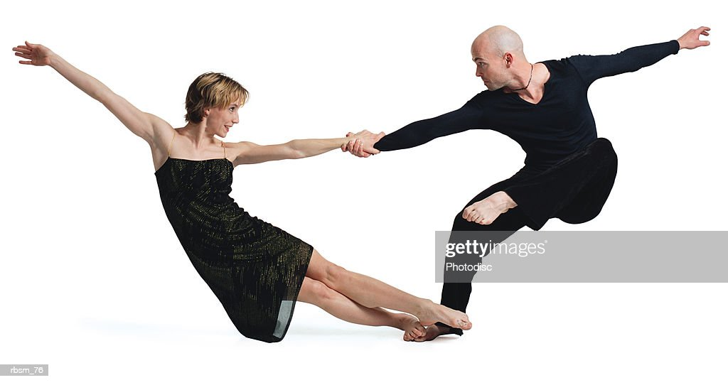 a caucasian couple dressed in black with a bald male and blonde female grasp each others hands as they outstretch their bodies and carefully balance themselves : Foto de stock